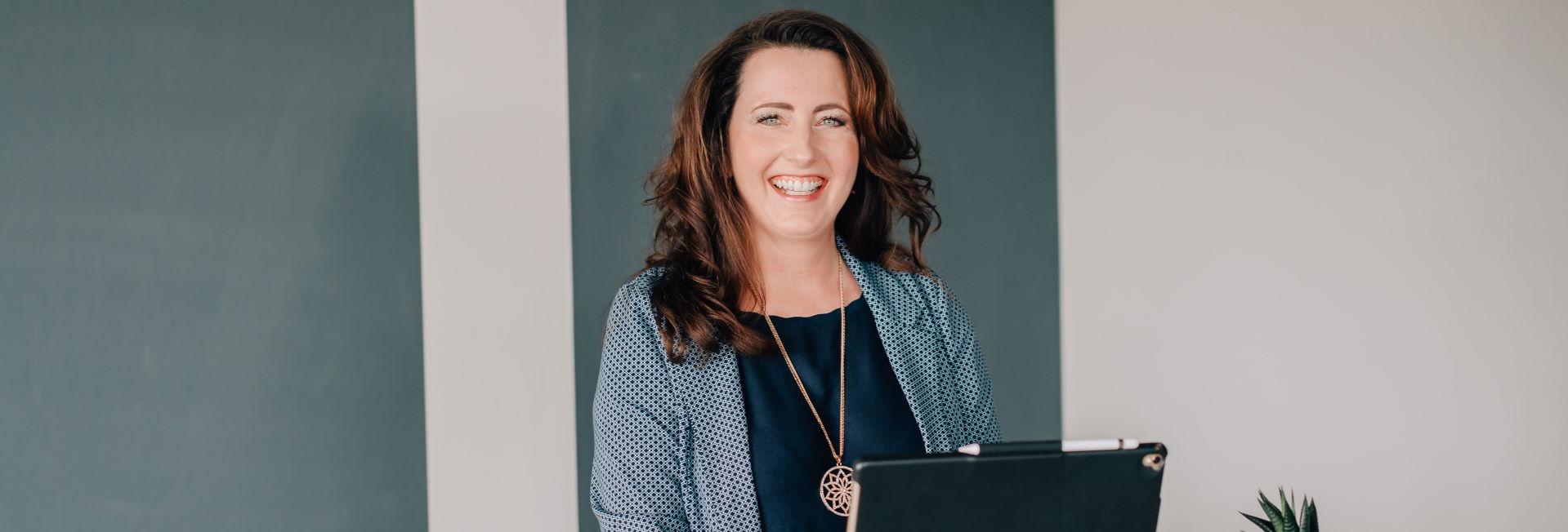 Tiergestütztes Training - Melanie Ebert steht lächelnd am Computer